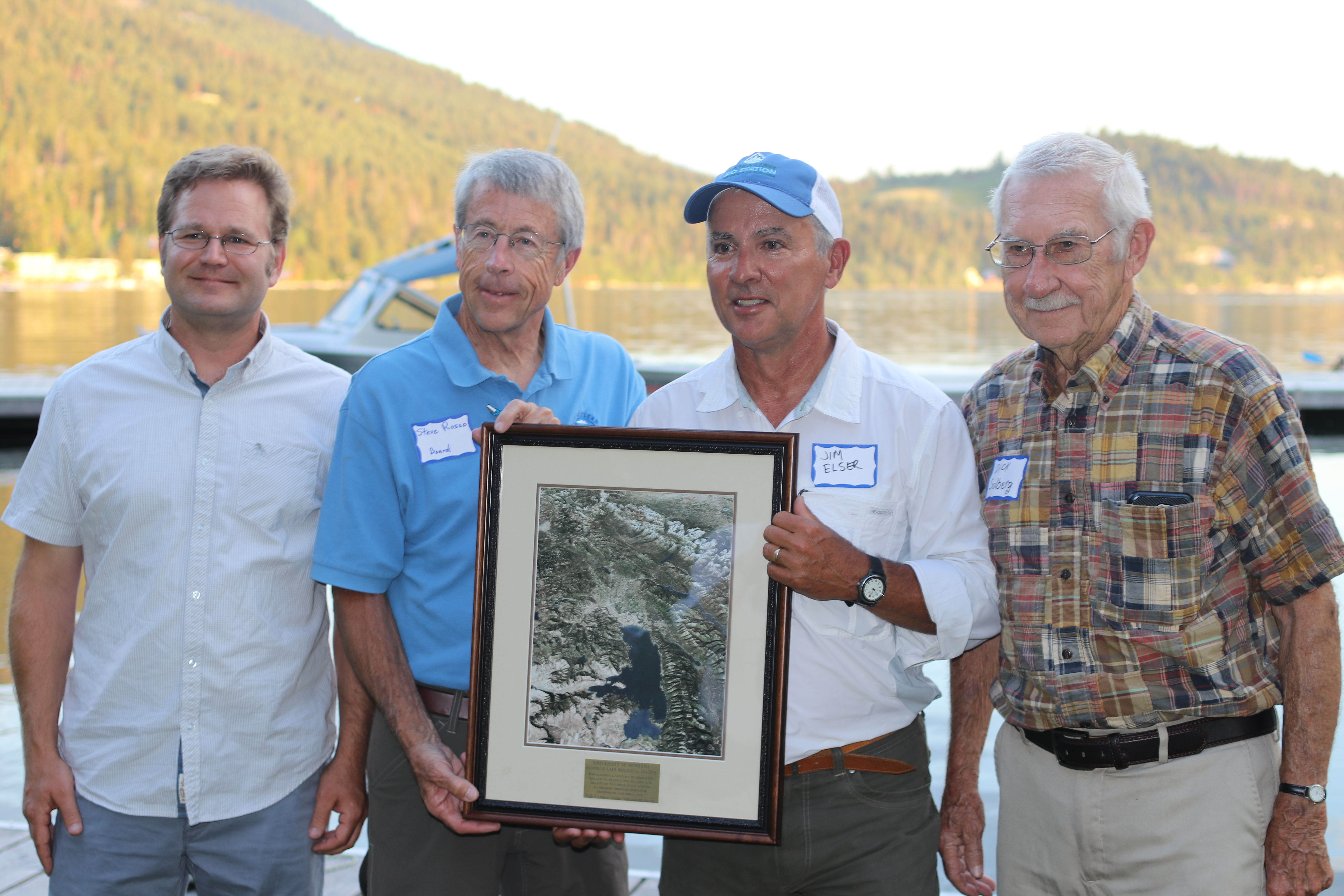 Flathead Lakers president Steve Rosso presents the 2018 Flathead Lakers Stewardship award to FLBS Assistant Director Tom Bansak, FLBS Director Jim Elser, and former FLBS Director Dick Solberg