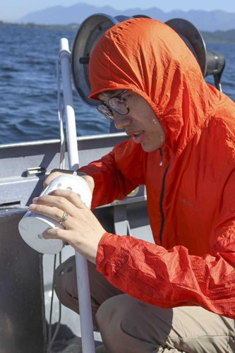 Visiting FLBS Researcher Xiong Xiong examines water sample on Jessie B research boat.