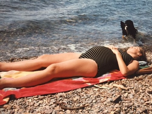 Pregnant woman sunbathing on beach, Ginny Miller