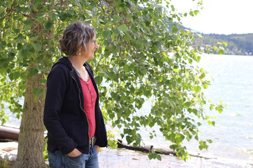 nanette nelson standing by a tree looking out at flathead lake